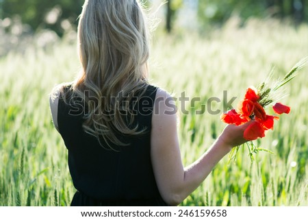 Woman collecting flowers outdoor - stock photo