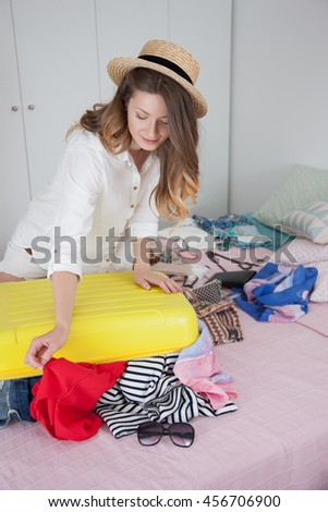 Woman collects a suitcase at home.girl in the bedroom, a lot of things, vacation and yellow suitcase.The woman collects a suitcase, things on the bed.Suitcase with things in the bedroom.Charges things - stock photo