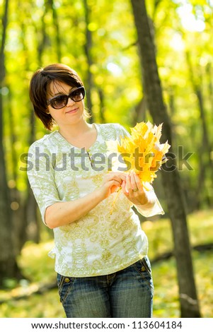 woman collects yellow leaves - stock photo