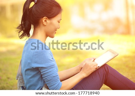 woman college student use tablet pc sit on grass  - stock photo