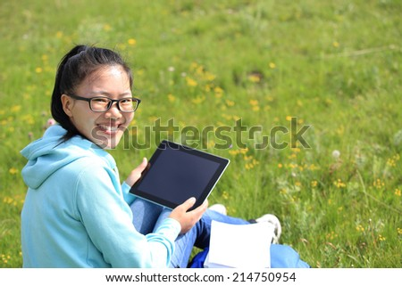 woman college student use tablet pc sit on grass