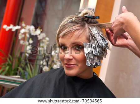 woman coloring her hair in hairdresser salon - stock photo