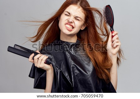 woman combs her hair comb on a gray background, straightening hair