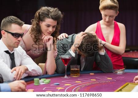 Woman comforting man losing at poker in casino - stock photo