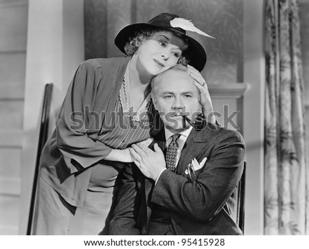 Woman comforting man smoking pipe - stock photo