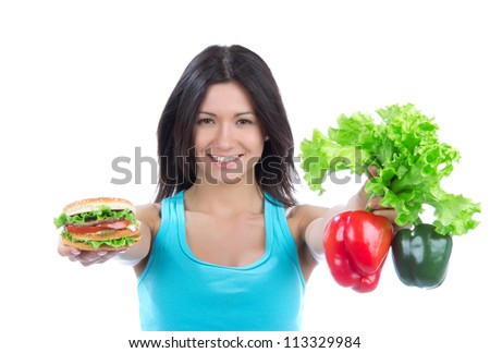 Woman comparing tasty fast food unhealthy burger or hamburger and healthy fresh peppers and salad isolated on a white background - stock photo