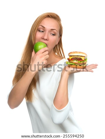 Woman comparing tasty unhealthy burger sandwich in hand and green apple getting ready to eat isolated on a white background Fast food concept