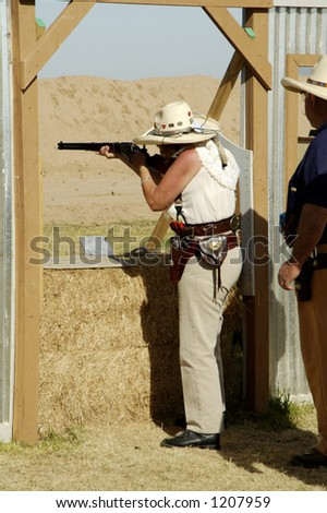 Woman competitor shooting a lever action rifle in a cowboy shoot competition. - stock photo