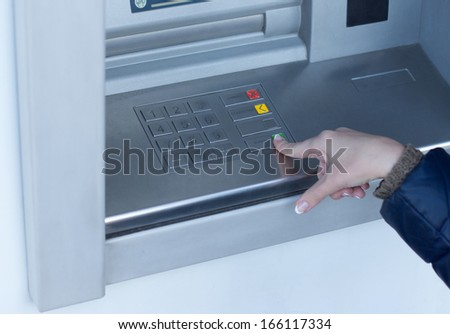 Woman completing a transaction on an ATM outside a bank as she withdraws cash for personal spending - stock photo