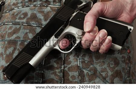 Woman conceals her gun - stock photo