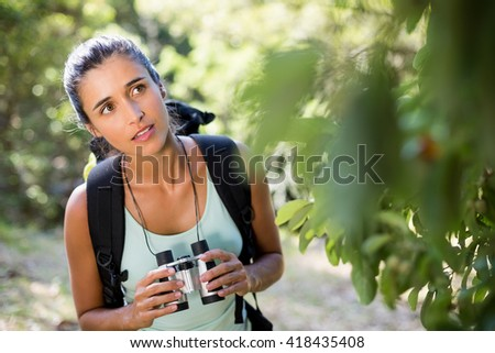 Woman concentrated holding binoculars on the wood - stock photo