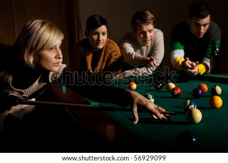 Woman concentrating on snooker game, leaning on table, aiming at ball, holding cue, friends watching in background.? - stock photo