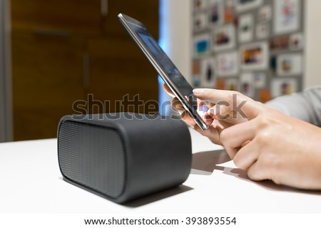 Woman connect their smart-phone to speakers. Nfc, bluetooth - stock photo