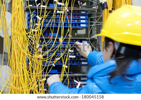 woman connecting network cables to switches - stock photo