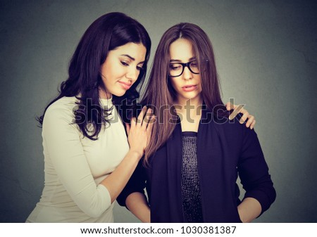 Woman consoling young sad friend helping to cope with problems.