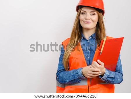 Woman construction worker builder structural engineerin in orange vest red hard helmet holds pen file pad. Safety in industrial work. Studio shot - stock photo