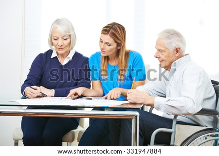 Woman consulting senior couple in nursing home - stock photo