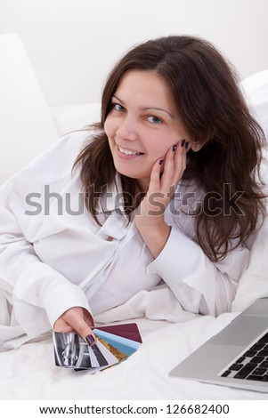 Woman contemplating a fistful of fanned credit cards with a serious expression as though unsure of the advisability of having so many - stock photo