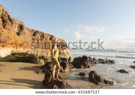 Woman contemplating sunrise on Cotovelo beach in Natal, RN, Brazil