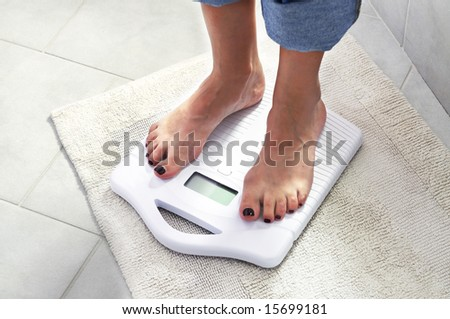 woman controlling her weight on a scale - stock photo