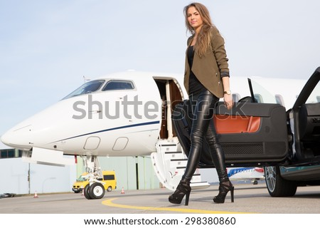 woman convertable car and corporate private jet - stock photo