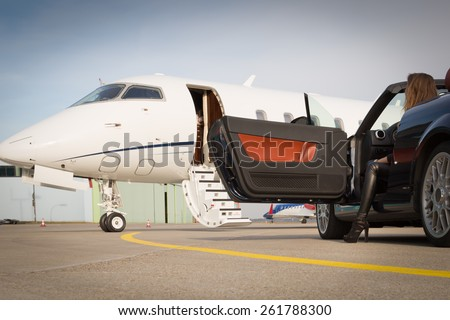 woman convertible car and corporate private jet - stock photo