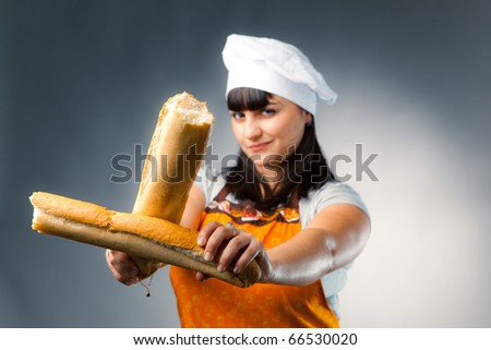 woman cook crossing a french bread, focus on the bread - stock photo