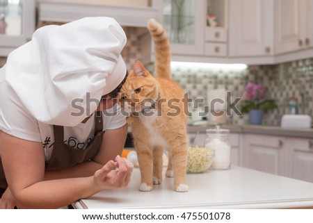 Woman - cook kissing a red cat in the kitchen