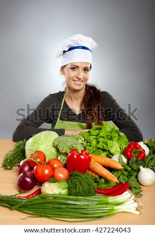 Woman cook with various vegetables in front of her on a wooden board