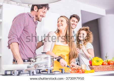 Woman cooking at home and laughing with her friends - Home party, housewife preparing dinner for her guests - stock photo
