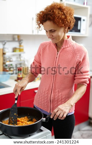 Woman cooking at home stir fry vegetables in the pan on the stove - stock photo