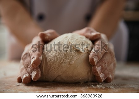 Woman cooking bread dough on wooden desk with flour. Home cuisine, handmade meal.  - stock photo