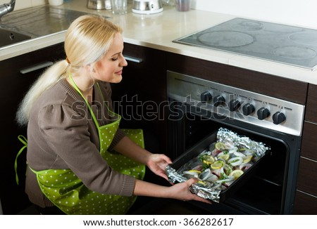 Woman cooking fish  in oven at home kitchen