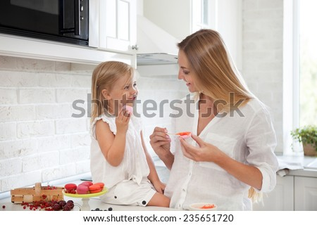 Woman cooking homemade macarons at the kitchen with her little daughter - stock photo