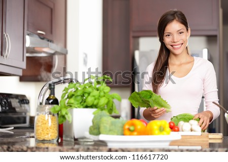 Woman cooking in new kitchen making healthy food with vegetables. Young multicultural Caucasian / Asian Chinese woman in her twenties. - stock photo
