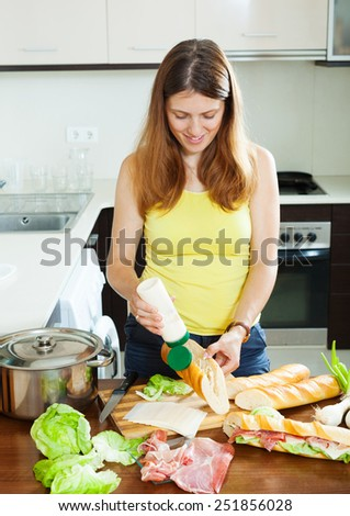woman cooking spanish sandwiches with mayonnaise  in home  kitchen