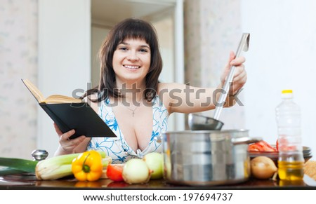 Woman cooking with cookbook and ladle in kitchen