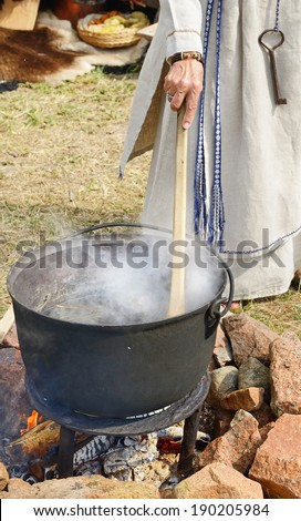 Woman cooks medical drink on a fire
