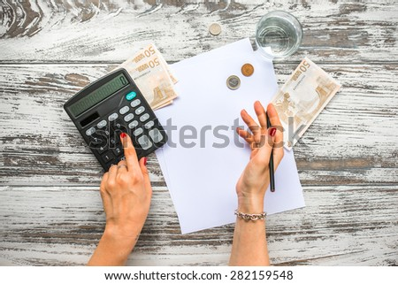 Woman counting euro money with calculator. Business concept. Top view - stock photo
