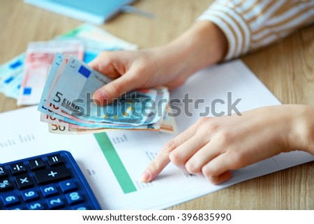 Woman counting money at the table - stock photo