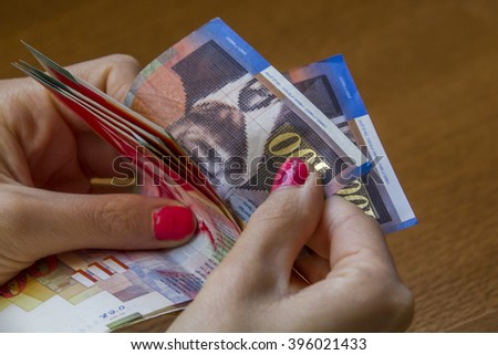 Woman counting money - Israeli New Sheqel banknotes.Concept photo of money, banking ,currency and foreign exchange rates.