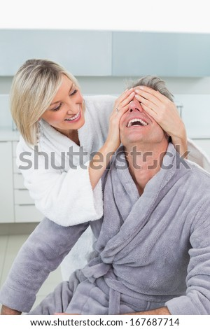 Woman covering a happy man's eyes from behind in the kitchen at home