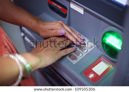 woman covering atm machine keypad with her hands and entering her pin number
