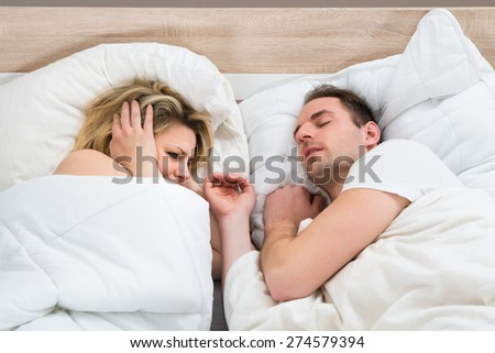 Woman Covering Ears While Man Snoring In Bed At Home - stock photo