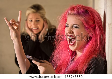 Woman covering ears while teenage girl sings