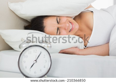 Woman covering ears with pillow in bed and alarm clock on side table