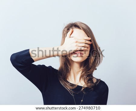woman covering her eyes isolated on a gray background - stock photo