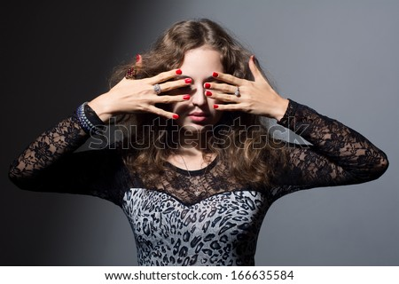 Woman covering her eyes with her hands on a gray background. Fear not to look. Fingers with red nails - stock photo