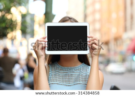 Woman covering her face with a blank tablet screen showing display - stock photo