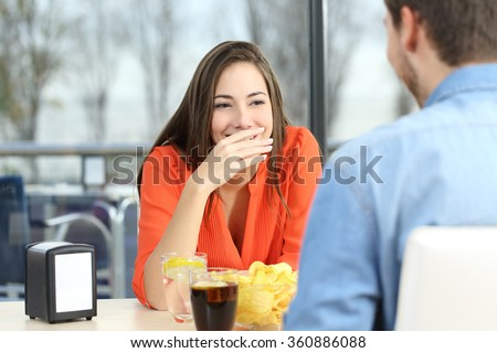 Woman covering her mouth to hide smile or bad breath during a date in a coffee shop with a window in the background - stock photo